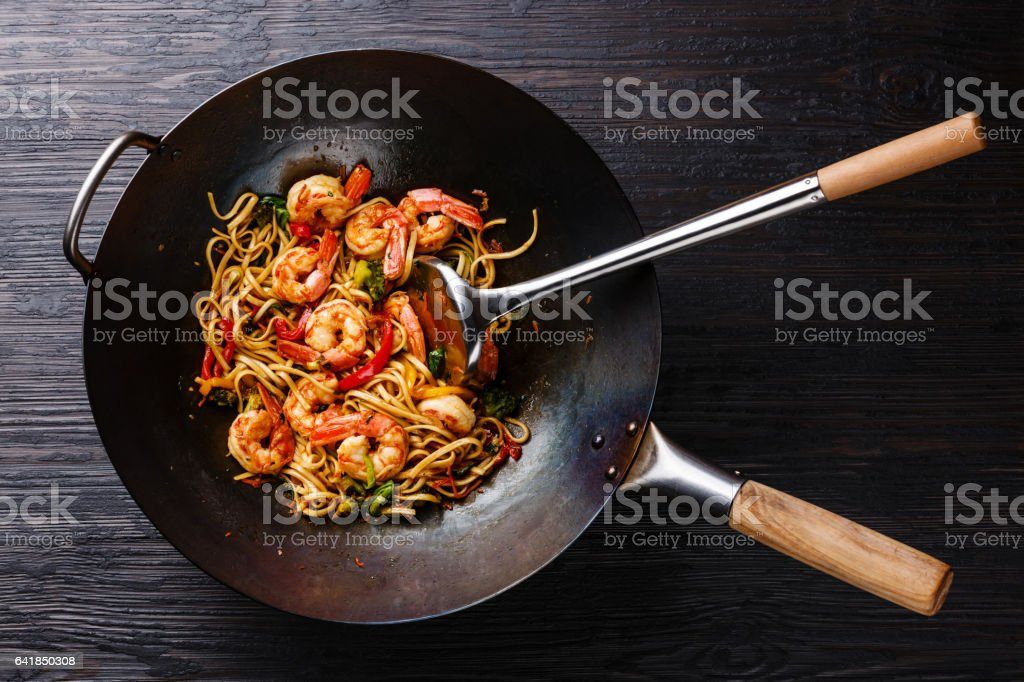 Udon stir-fry noodles with shrimp and vegetables in wok pan stock photo