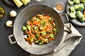 Stir-fry vegetables with noodles in wok pan on dark stone background. Top view, flat lay