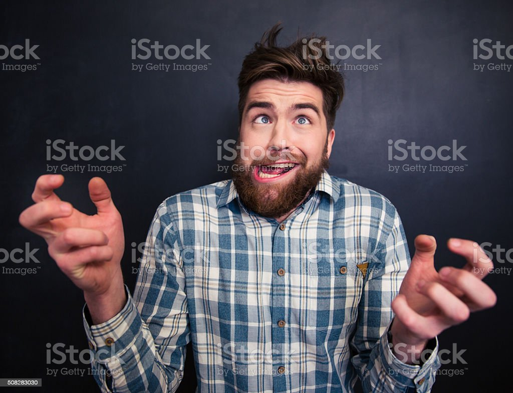 Ugly bearded man grimacing over black background stock photo