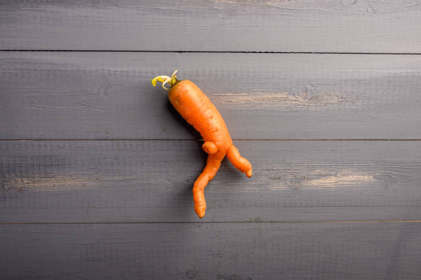ugly carrot concept on wooden background. copy space - disfigure stock pictures, royalty-free photos & images
