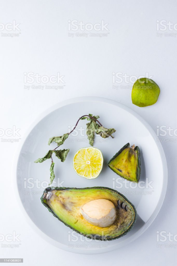 Ugly food on white background. Ugly rotten avocado on white plate....