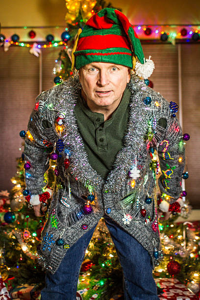 Ugly Sweater Elf A Caucasian man wearing an ugly cardigan holiday sweater, and an elf hat, with a decorated tree in the background. ugliness stock pictures, royalty-free photos & images