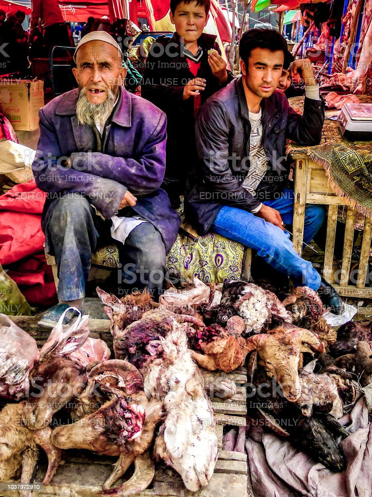 Uighur men and goats head at a market near Kashgar on the silk road in China stock photo