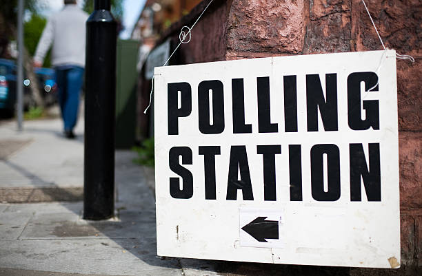 a uk polling station sign hooked on a wall on a street - polling place stock pictures, royalty-free photos & images