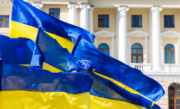 ukraine blue yellow flags evolving on a wind near town hall classic architecture building with columns arch windows and soft pink and white walls, independence and revolution of dignity concept - ucrânia imagens e fotografias de stock
