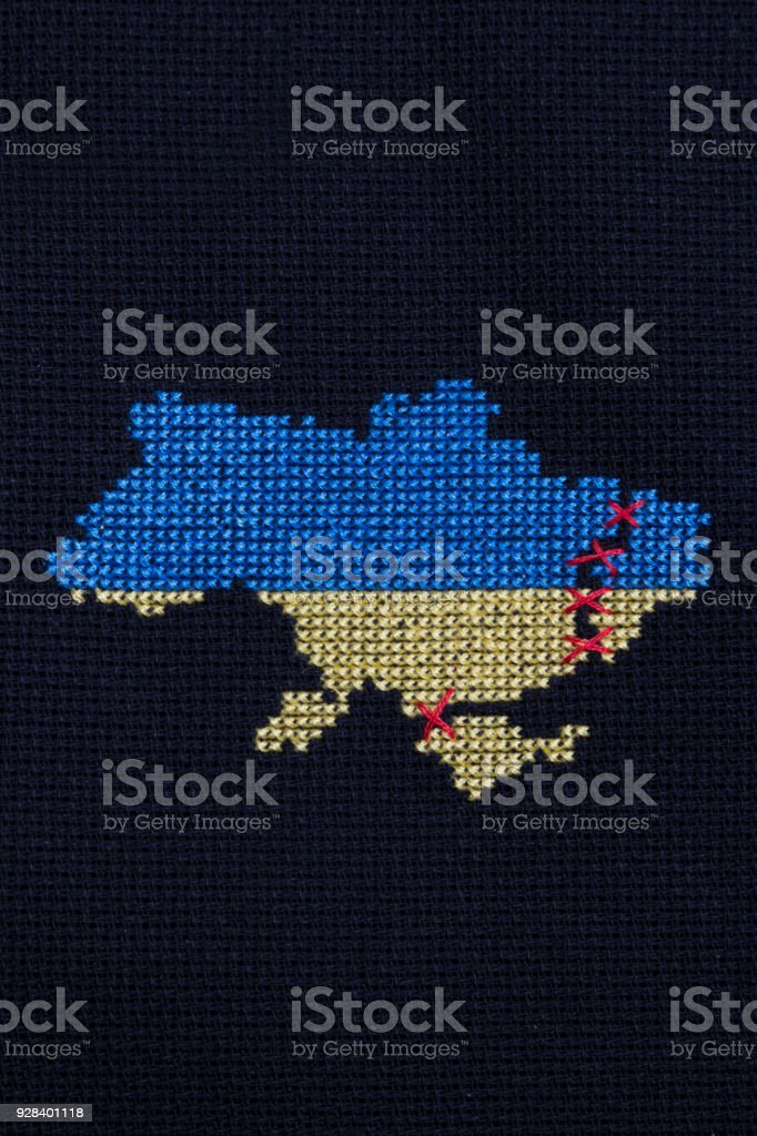 Ukraine embroidered with yellow and blue threads. In the east of the country is a black border, connected by red threads. stock photo
