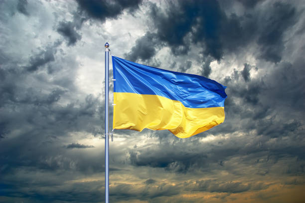 Ukraine flag. Ukrainian flag on black storm cloud sky. stormy weather stock photo