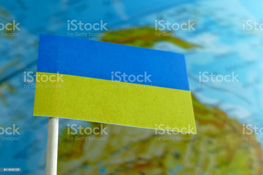 Ukraine flag with a globe map as a background macro stock photo