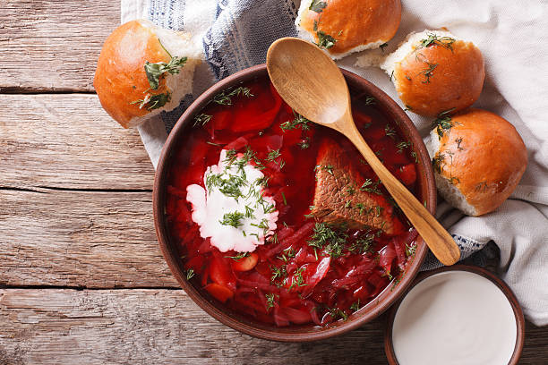 Ukrainian borsch soup and garlic buns on the table. Horizontal stock photo