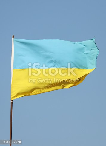 Ukrainian flag flying on flagpole on blue sky background