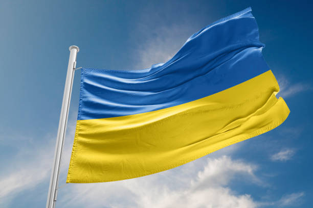 Ukrainian Flag is Waving Against Blue Sky stock photo