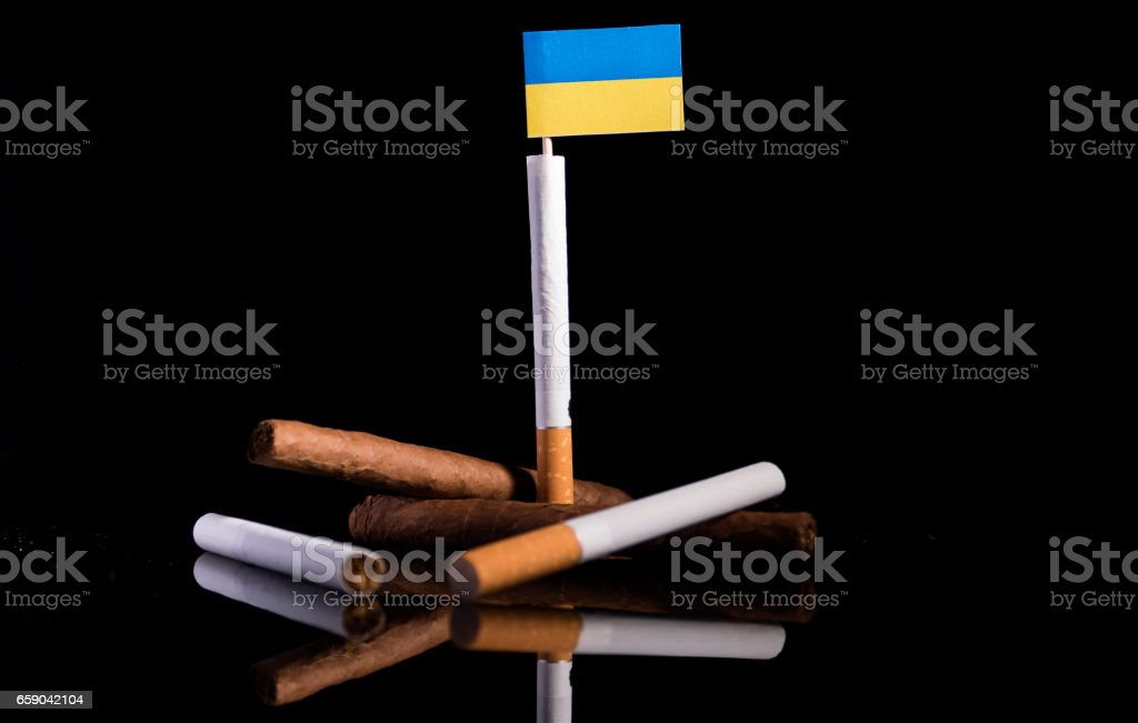 Ukrainian flag with cigarettes and cigars. Tobacco Industry concept. royalty-free stock photo