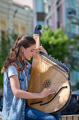 KIEV, UKRAINE - MAY 05, 2018 : Ukrainian girl playing the harp on the street of Kiev for passersby, Ukraine