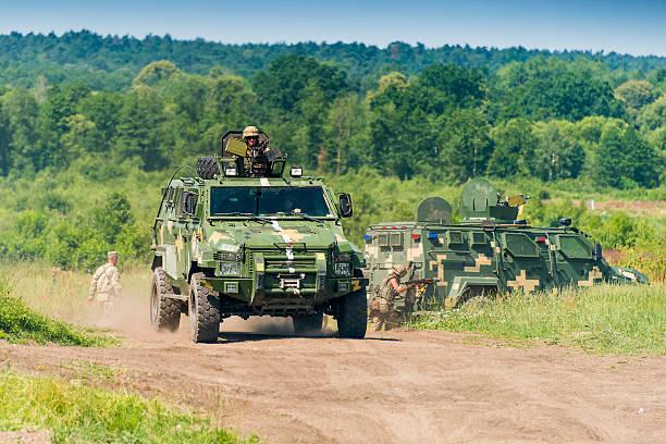 Ukrainian military vehicle KrAZ Spartan with comandos attack sim stock photo