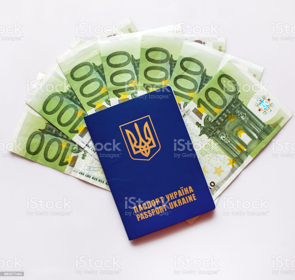 Ukrainian passport for travel abroad on a background of euro banknotes (visa regime for Ukrainian, green light for Ukraine, open Europe - concept) royalty free stockfoto