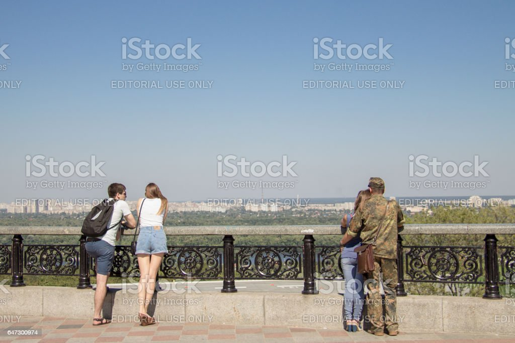 Kiev, Ukraine - August 8, 2015: Ukrainian soldier on leave from the Eastern Ukraine conflict observing Kiev panorama with his girlfriend stock photo