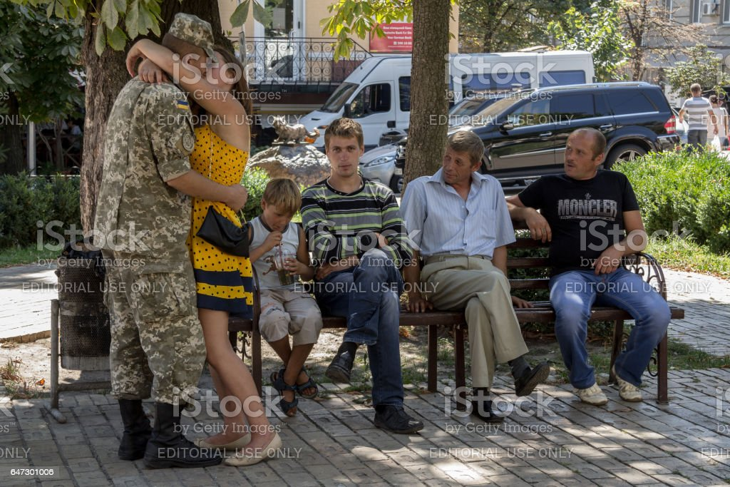 Kiev, Ukraine - August 9, 2015: Ukrainian soldier on leave from the Eastern Ukraine conflict kissing his girlfriend next to his relatives stock photo