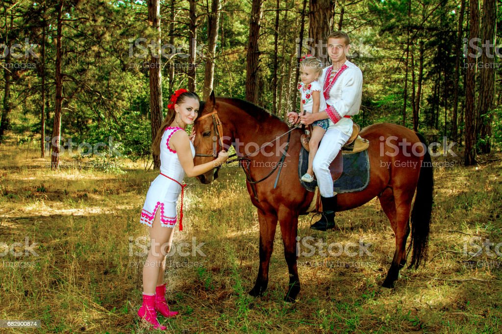 Ukrainians mom and dad daughter ride in the woods on horseback stock photo
