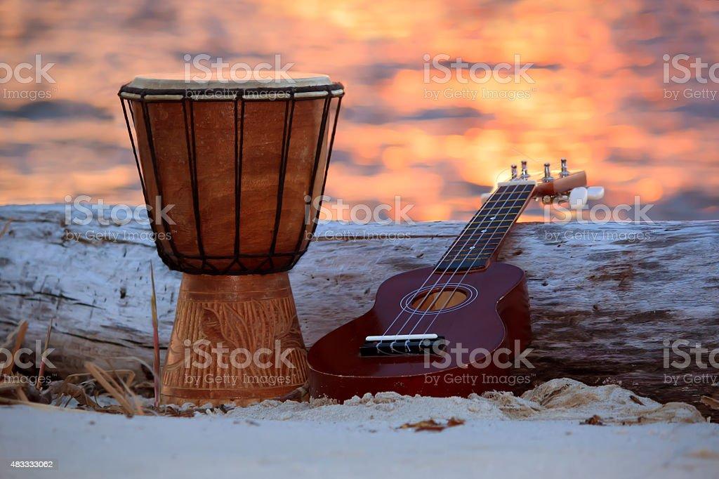 Ukulele and ethnic drum over a sunset beach. stock photo