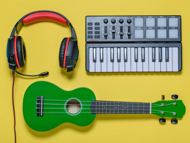 Ukulele and wired blue microphone on yellow background. The view from the top. stock photo