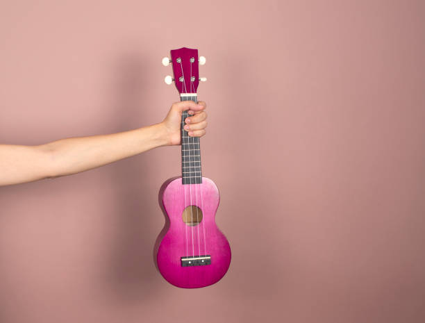 Ukulele in outstretched female hand on a pink background. Place for text stock photo