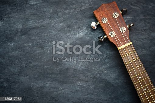 Ukulele on black cement background. Headstock and fret of ukulele parts. Copy space for text. Concept of Hawaiian musical instruments and music lovers.