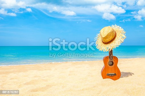 istock Ukulele on the beautiful summer beach wiht copy space and blue sky 681876282