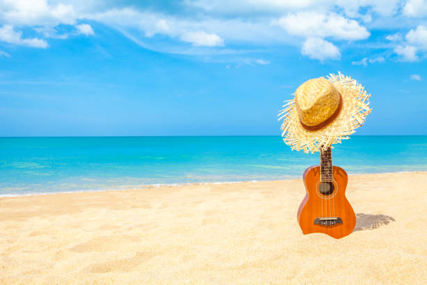 Ukulele on the beautiful summer beach wiht copy space and blue sky stock photo
