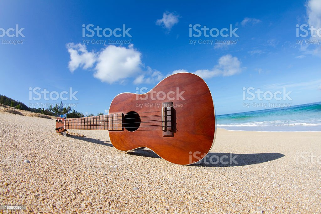 A ukulele sitting on its side on a Hawaiian beach stock photo
