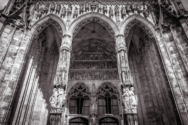 Ulm Minster or Cathedral of Ulm city, Germany. It is top landmark of Ulm. Front view of ornate entrance of old Gothic cathedral, Ulm Minster or Cathedral of Ulm city, Germany. It is top landmark of Ulm. Front view of ornate entrance of old Gothic cathedral, luxury facade of famous medieval Christian church in black and white. ulm minster stock pictures, royalty-free photos & images