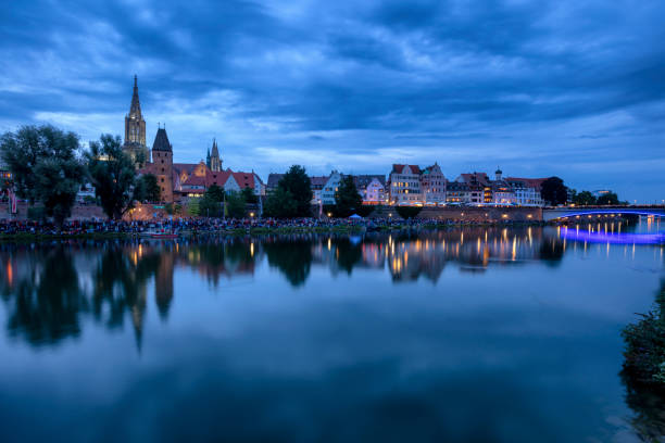 Ulm, skyline at night Ulm skyline and crowd of spectators at night during the traditional Light Serenade Festival, view over Danube River ulm stock pictures, royalty-free photos & images