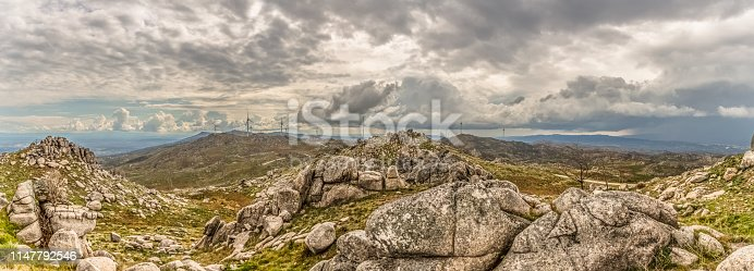 Ultra panoramic view at the Caramulo Mountains, and wind turbines on top of mountains and dramatic sky as background, in Portugal