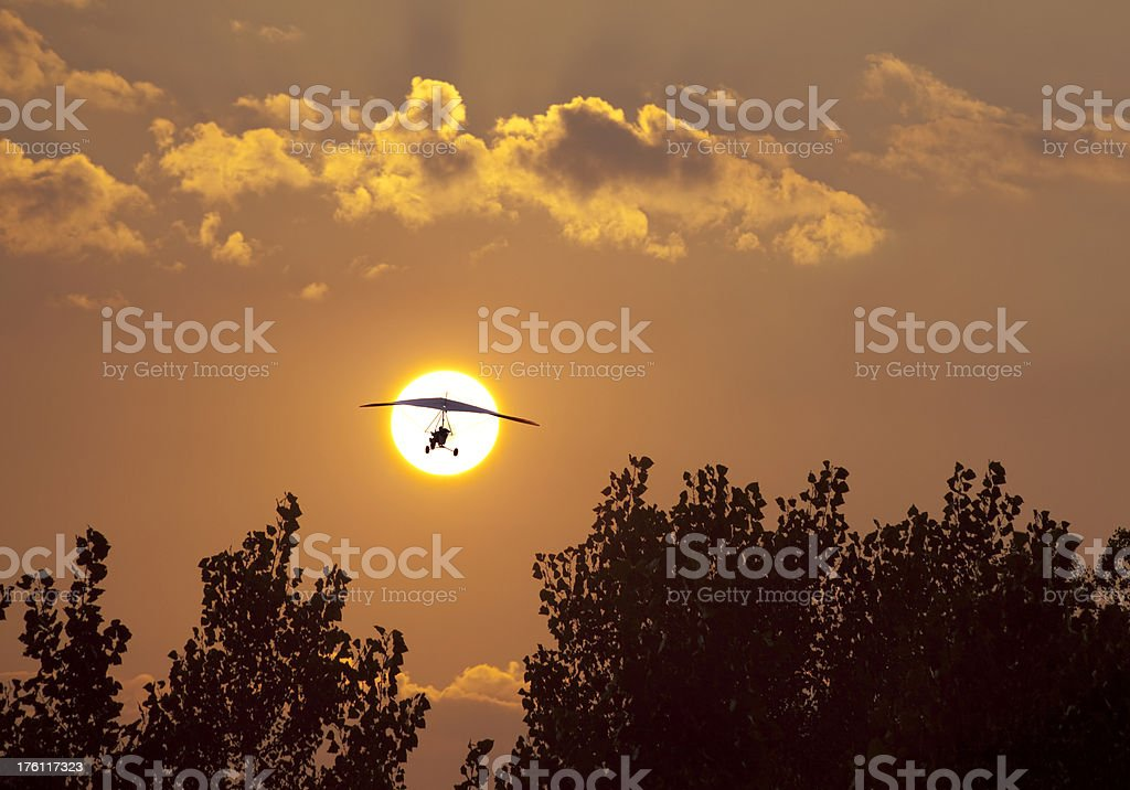 Ultralight Airplane Flying Off Into the Setting Sun royalty-free stock photo