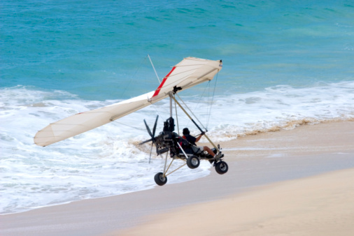 Ultralight Flying Coming In For A Landing On The Beach Stock Photo - Download Image Now
