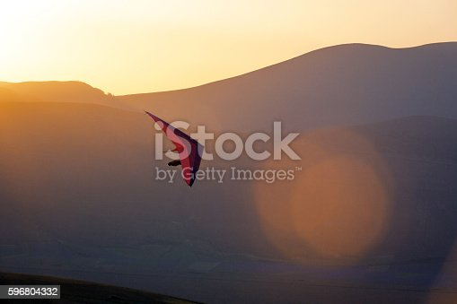 An ultralight plane against sunset sky ,hang Glider Pilot Launching,lens flare,Castelluccio,Apennines,Italy,Nikon D3x