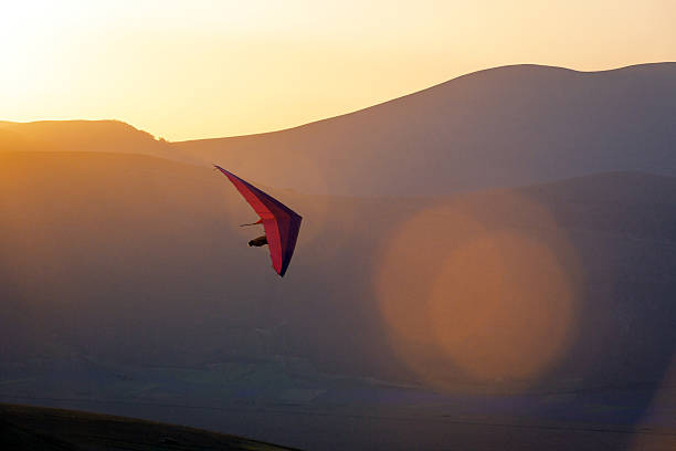 Ultralight -Hang Glider Pilot Launching,lens flare,Castelluccio,Apennines,Italy An ultralight plane against sunset sky ,hang Glider Pilot Launching,lens flare,Castelluccio,Apennines,Italy,Nikon D3x aerodynamic stock pictures, royalty-free photos & images