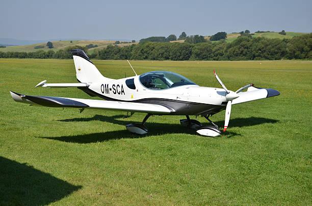 Ultralight propeller-driven PS-28 Cruiser airplane stands on grass landing strip - foto de stock