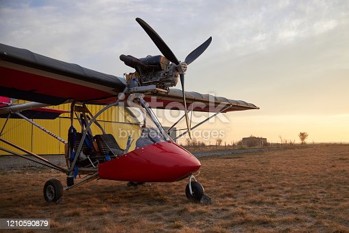 Ultralight two-seater airplane with a propeller stands on the airfield against the background of a hangar