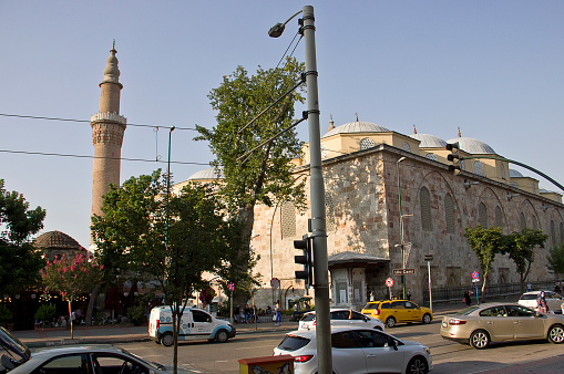 Bursa, Turkey - July 18, 2020: View of ulu mosque and central road, people in the courtyard of Grand Mosque- Ulu Cami for worshippers gather. The mosque is most important mosque in Bursa and a landmark of early Ottoman architecture built in 1399.