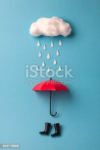 umbrella and rain boots under the cloud on sky blue background.