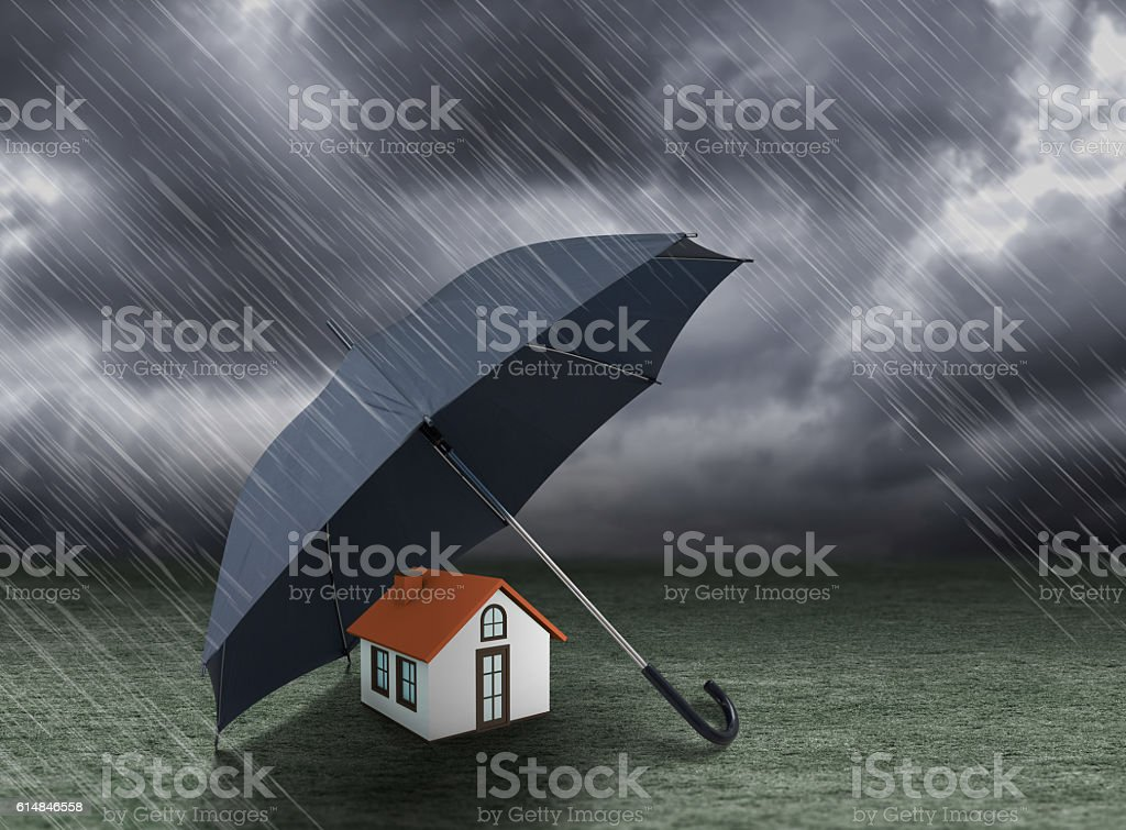 umbrella covering home under heavy rain, insurance concept stock photo