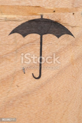 istock umbrella icon, black spray on plywood texture background 502382111