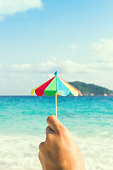 Umbrella in hand on background of ocean. Hand made, origami. Thailand, Similan Islands. Vertically