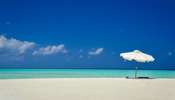 Sonnenschirm am idyllischen tropischen Sandstrand. Weißen Strand Sonnenschirm und blauer Himmel. Sonne und Sonnenschirm am Strand. Sommer Strand Landschaft. – Foto