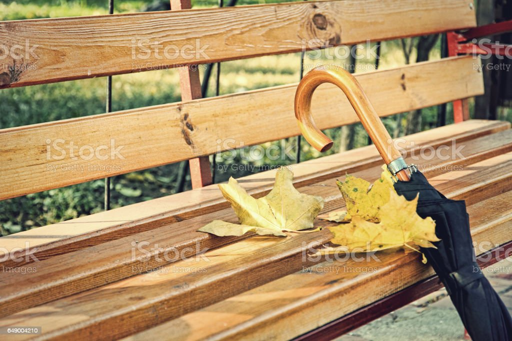 Umbrella on wooden park bench taken closeup. - foto de stock
