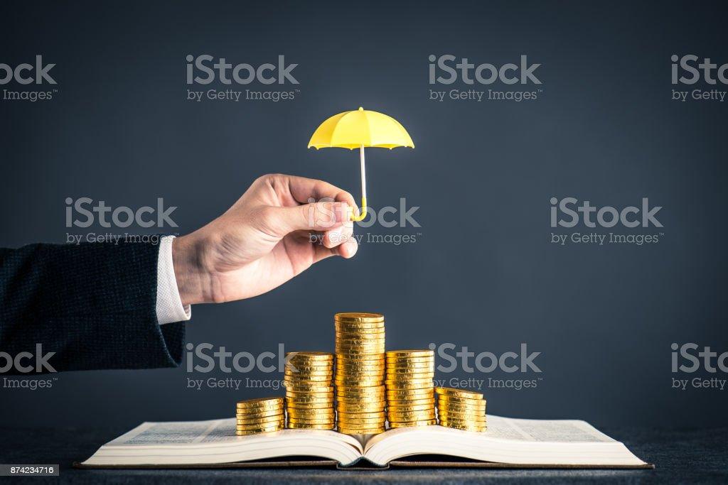 umbrella protecting gold coins stock photo