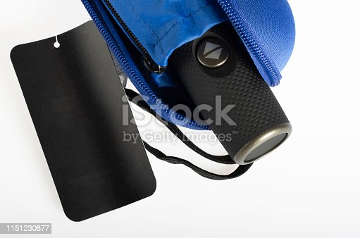 Compact waterproof umbrella with sleeve in hard case isolated on white with a black tag label.