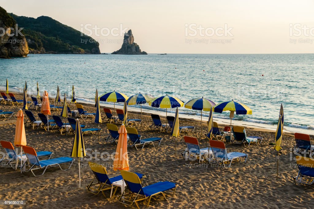 Umbrellas And Closed Parasols At Beach Next To Ionian Sea During Sunset royalty-free stock photo