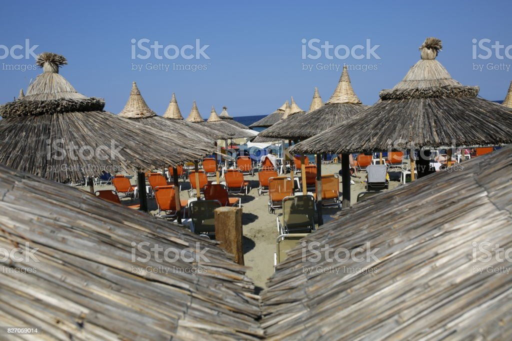 Umbrellas and sunbeds by the beach stock photo