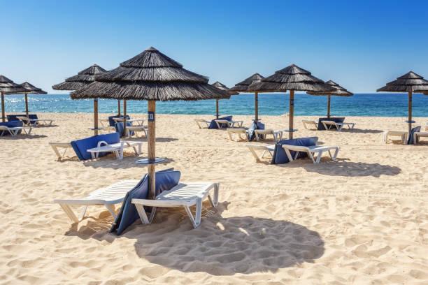 Umbrellas and sunbeds on the southern beach of the Algarve. Portugal. stock photo